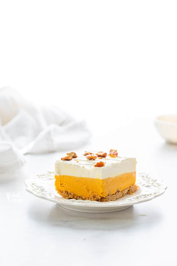 a slice of gluten free pumpkin lush cake on a white plate with a white linen crumpled in the background