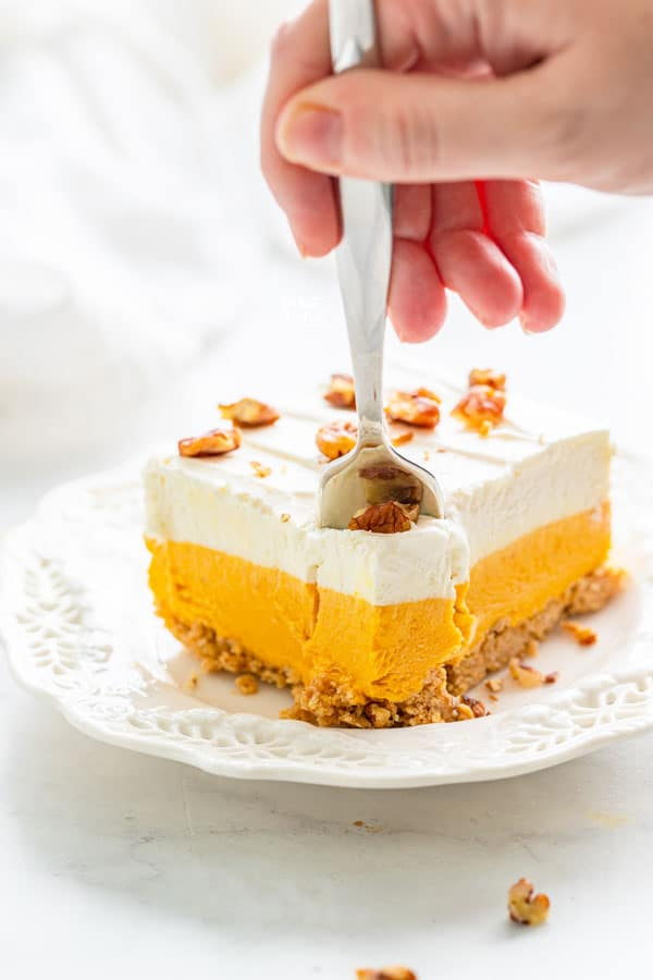 a slice of gluten free pumpkin lush cake on a white plate with a hand using a fork to remove a bite