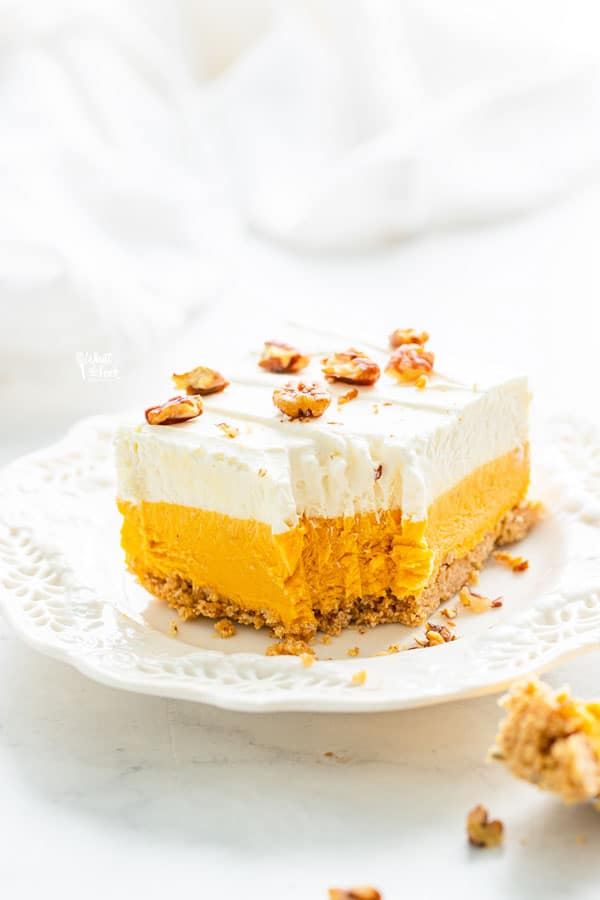 a pice of gluten free pumpkin lush cake on a white plate with a forkful removed