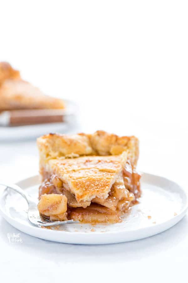 a slice of gluten free apple pie on a small white plate with a bite taken out