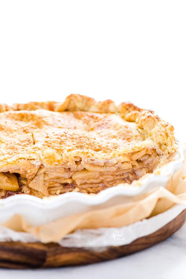 Straight on shot of a gluten free apple pie that's been sliced into showing the layers of apples in the flaky crust