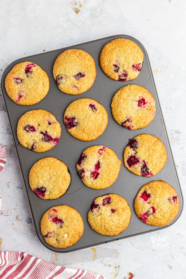 baked gluten free white chocolate cranberry muffins in a metal muffin tin