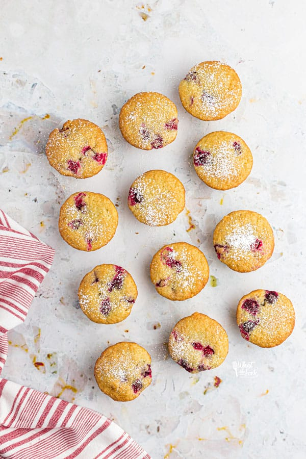 one dozen gluten free white chocolate cranberry muffins on a white board dusted with powdered sugar