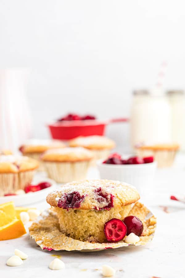 a gluten free white chocolate cranberry muffin in a paper liner that's starting to be unwrapped garnished with fresh cranberries