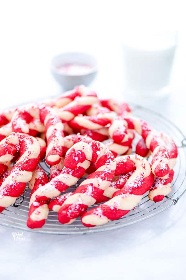 a pile of gluten free candy cane cookies on a round. metal wire rack