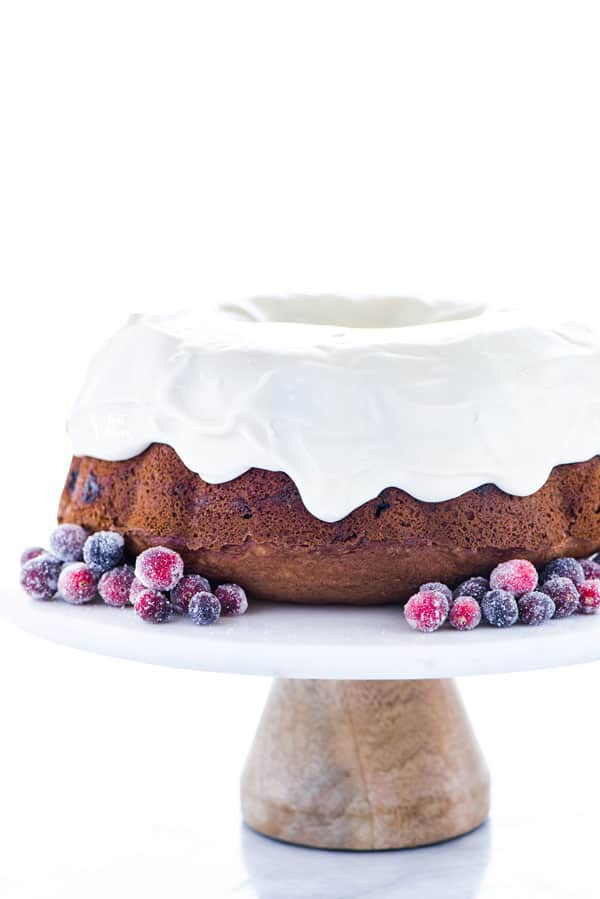 a gluten free cranberry orange bundt cake garnished with sugared cranberries on a white cake stand with a wood base