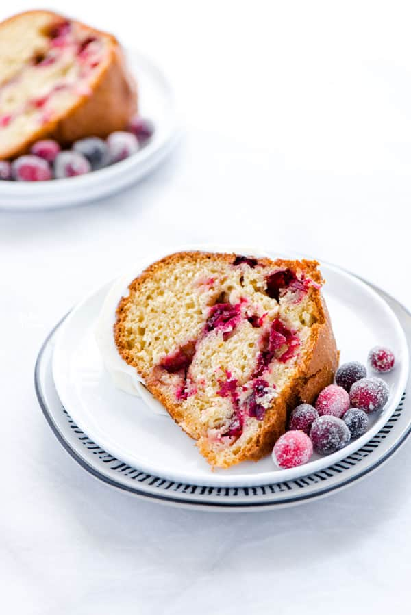 a slice of gluten free cranberry orange bundt cake on a small white plate garnished with sugared cranberries