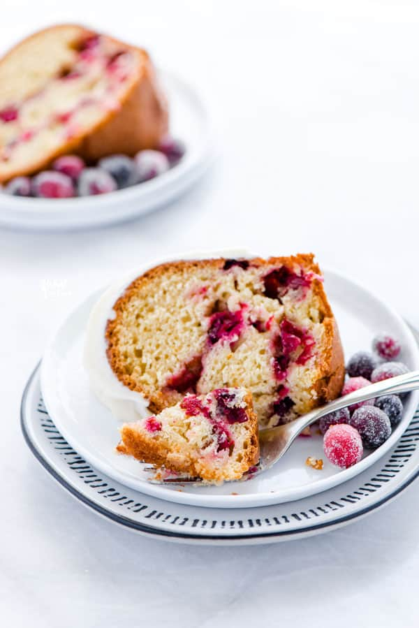 a slice of gluten free cranberry orange bundt cake on a small white plate with a small bite of cake on a fork