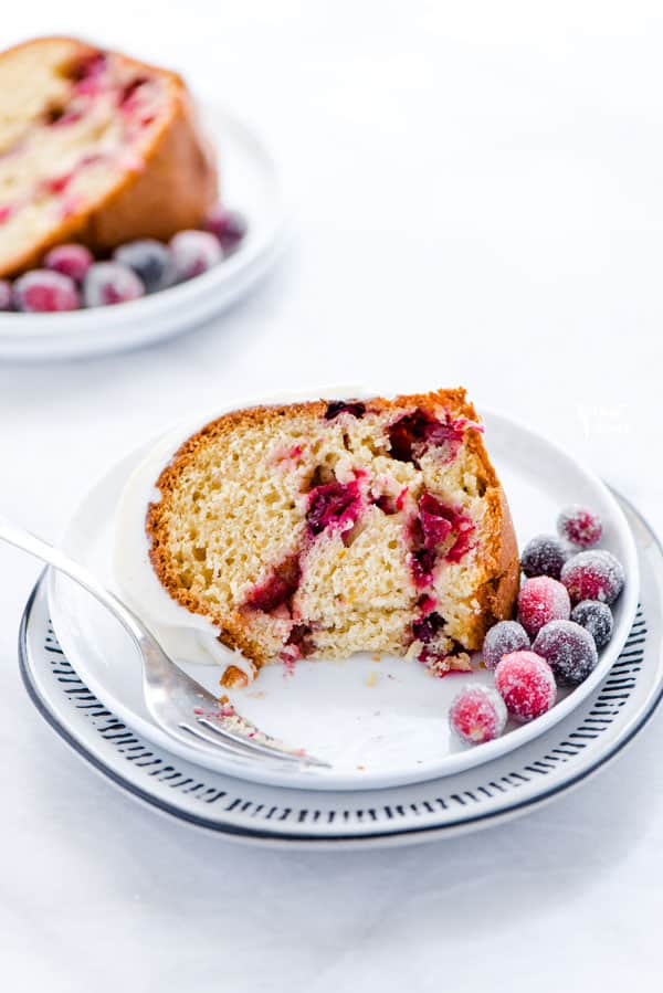 a piece of gluten free cranberry orange bundt cake on a small white plate with a bite taken out