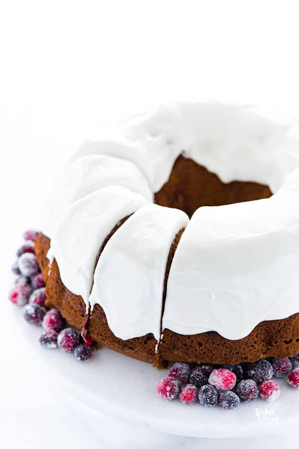 sliced gluten free cranberry orange bundt cake on a white cake stand garnished with sugared cranberries