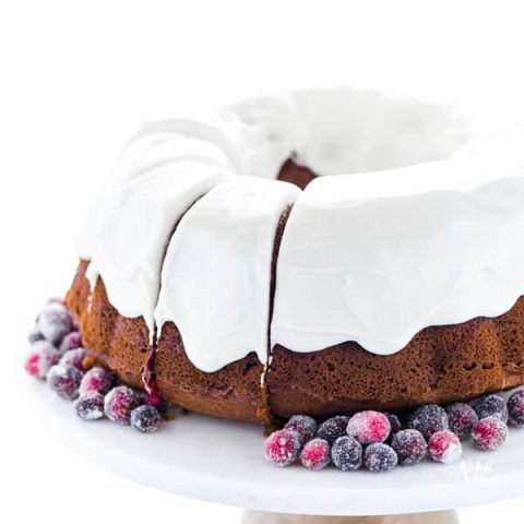 a gluten free cranberry bundt cake with cream cheese icing on a white marble cake stand with wood base garnished with sugared cranberries