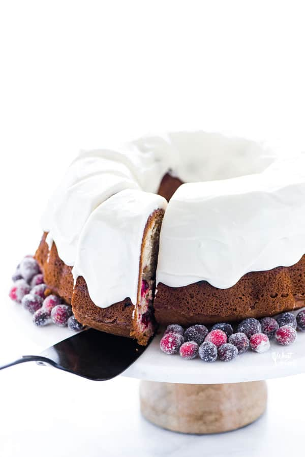 a slice of gluten free cranberry orange bundt cake being served with a black cake server