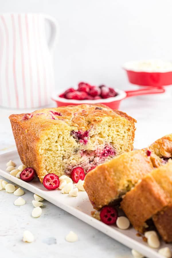 a loaf of gluten free white chocolate cranberry bread on a white plate that's been sliced into
