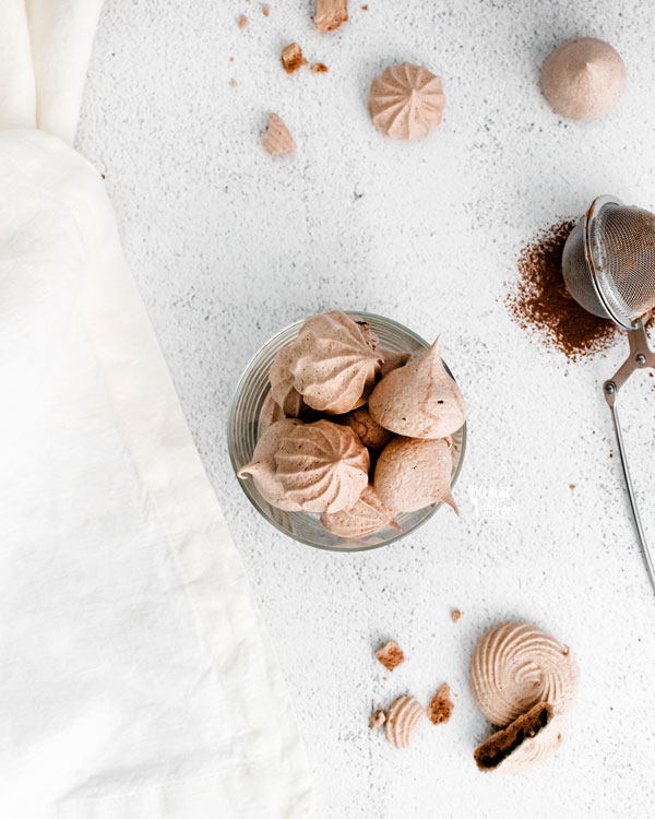overheard shot of dark chocolate meringue cookies in a round class cup on a white backdrop surrounded by a white towel, more chocolate meringue cookies, and a tea ball filled with cocoa powder