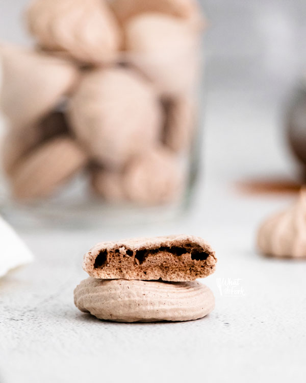 two dark chocolate meringue cookies stacked on top of each other with the top one cut in half to show the interior