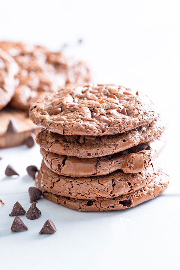 A stack of 5 flourless chocolate cookies garnished with chocolate chips scattered around