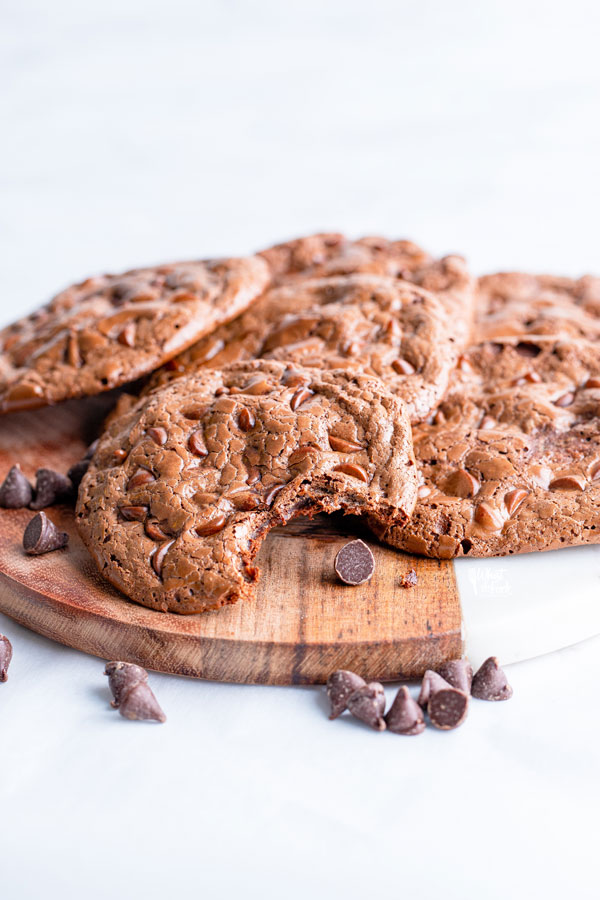 flourless chocolate cookies on a wood and marble board garnished with chocolate chips