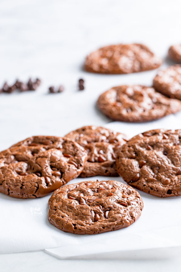 flourless chocolate cookies on a white surface with more cookies and chocolate chips in the background