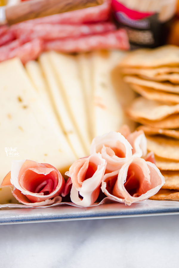 closeup of prosciutto roses on a charcuterie board