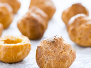 round gluten free choux pastry shells on a marble board covered in wax paper