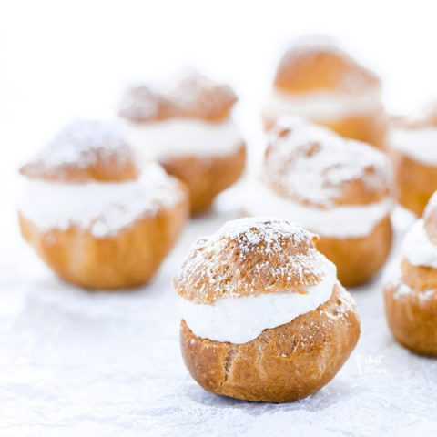 gluten free Choux Pastry shells filled with whipped cream and topped with powdered sugar for Cream Puffs