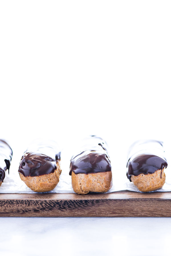 gluten free chocolate eclairs lined up on a wood board lined with wax paper