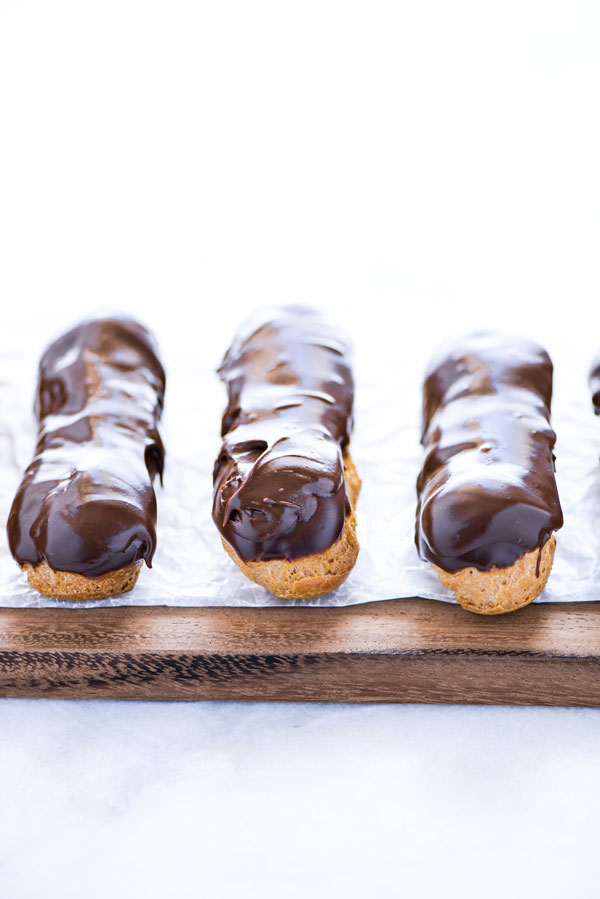 finished gluten free chocolate eclair recipe on a wax paper lined wood cutting board