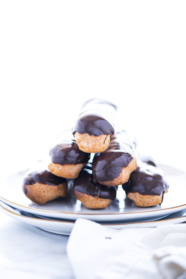 Classic Gluten Free Chocolate Eclair Recipe ready to serve on a stack of gold rimmed white plates