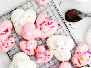 overhead shot of a finished heart meringue cookie recipe with pink and white heart meringues topped with Valentine's Day sprinkles