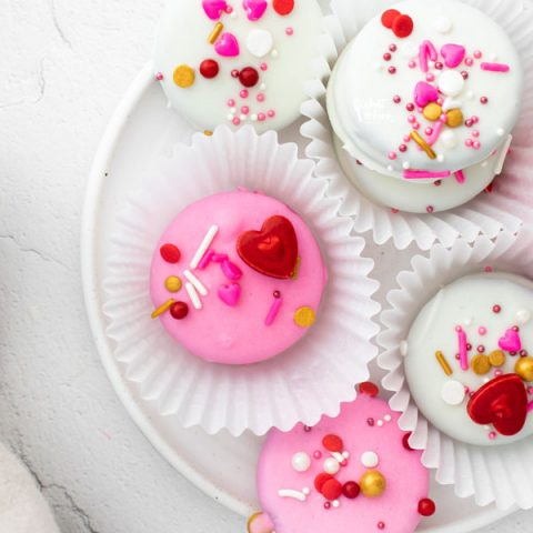 overhead shot of pink and white Valentine's Chocolate Covered Oreos in white paper holders on a white plate