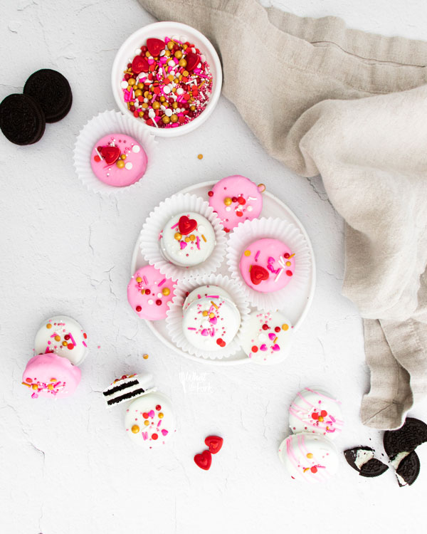 overheard shot of Valentine's Chocolate Covered Oreos on a white plate and scattered on a white surface