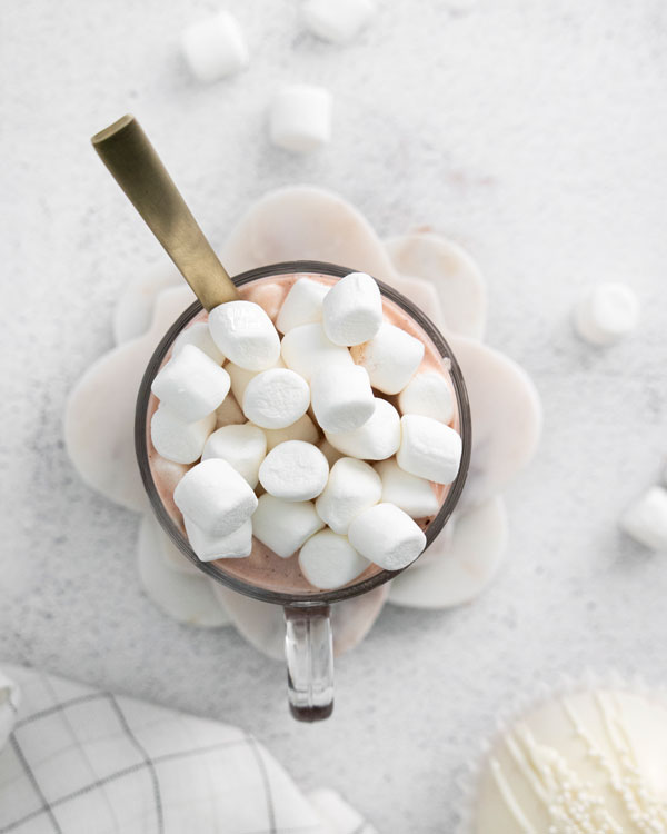 overhead shot of hot cocoa in a clear glass mug with a gold spoon garnished with a pile of mini marshmallows
