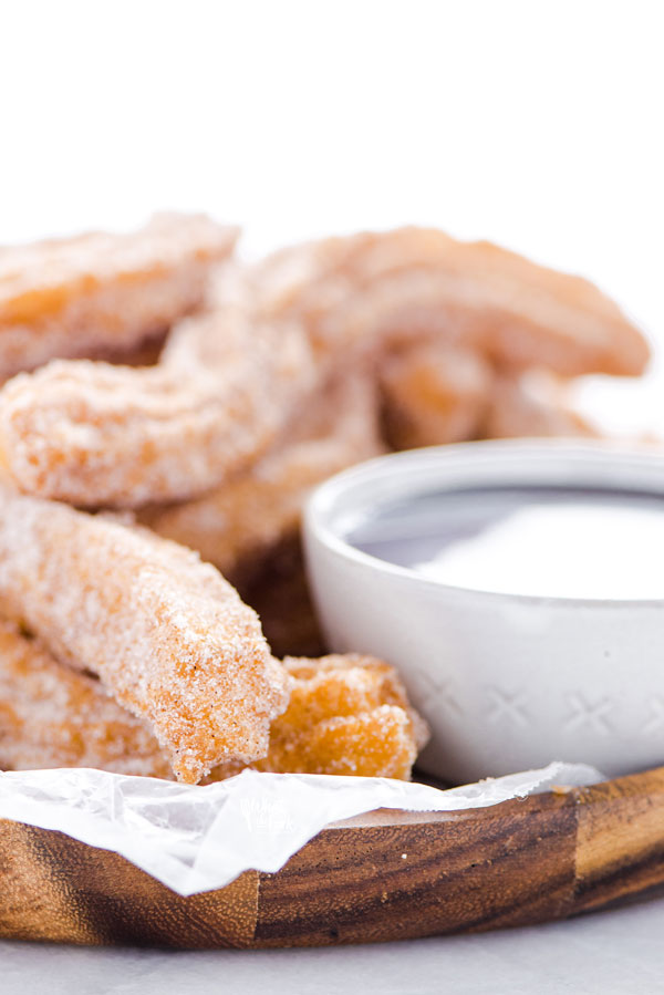 close up of gluten free churros on a wood platter lined with wax paper