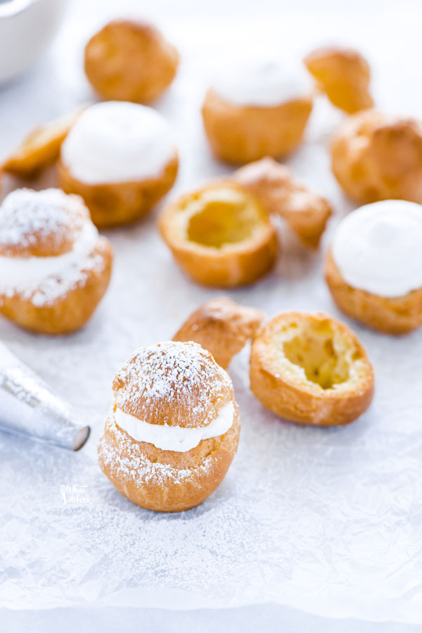 gluten free cream puffs on wax paper being filled with whipped cream