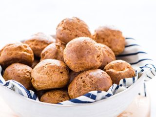 a white bowl lined with a blue striped towel filled with gluten free Gougères