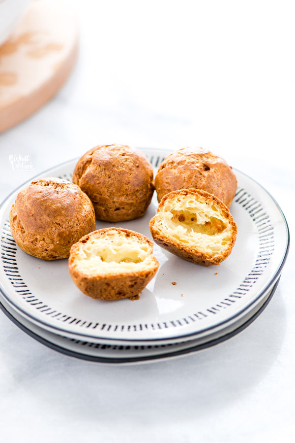 gluten free Gougères on a stack of white plates with one cut in half to show the inside