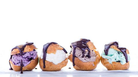 gluten free profiteroles filled with different flavors of ice cream, topped with chocolate ganache, and lined up on a white marble surface