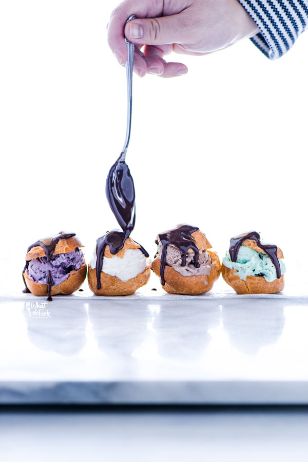 gluten free profiteroles filled with different flavors of ice cream being topped with chocolate ganache