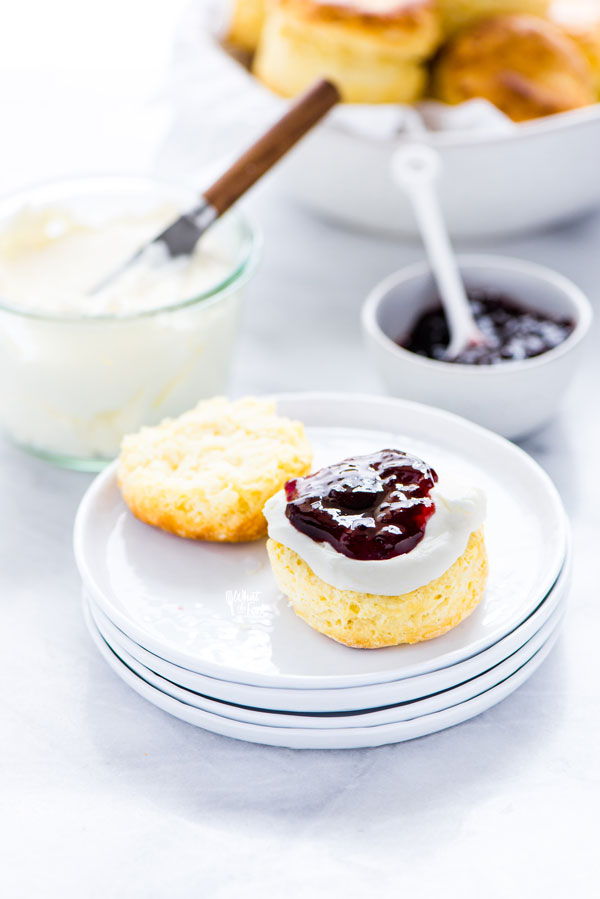 a gluten free scone on a stack of white plates that's been split in half and topped with clotted cream and jam