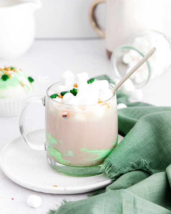 hot cocoa in a clear glass mug made with a St. Patrick's Day hot chocolate bomb