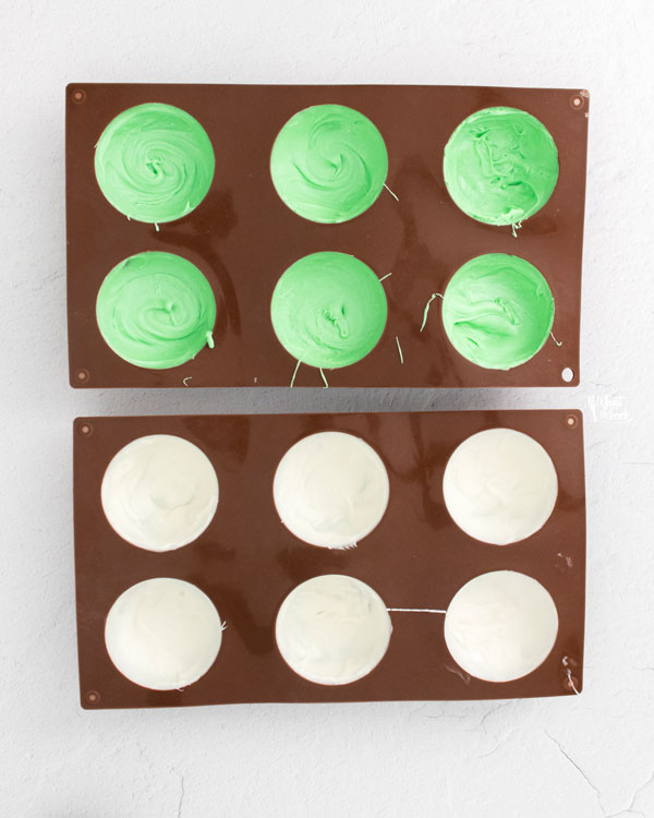 green and white chocolate in round molds to make St. Patrick's Day Hot Cocoa Bombs