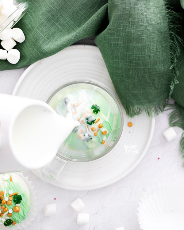 hot milk being poured over a green St. Patrick's Day Hot Chocolate Bomb in a clear glass mug