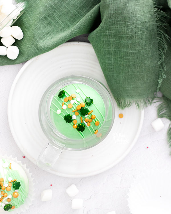 green St. Patrick's Day Hot Cocoa Bombs in a clear mug on a white plate
