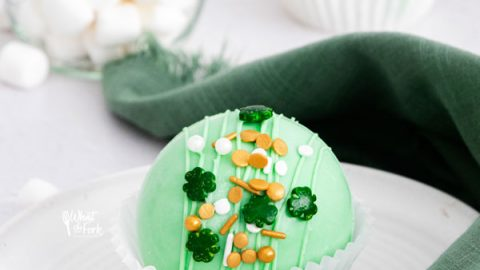 a green St. Patrick's Day Hot Cocoa Bombs in a white paper liner on a white plate