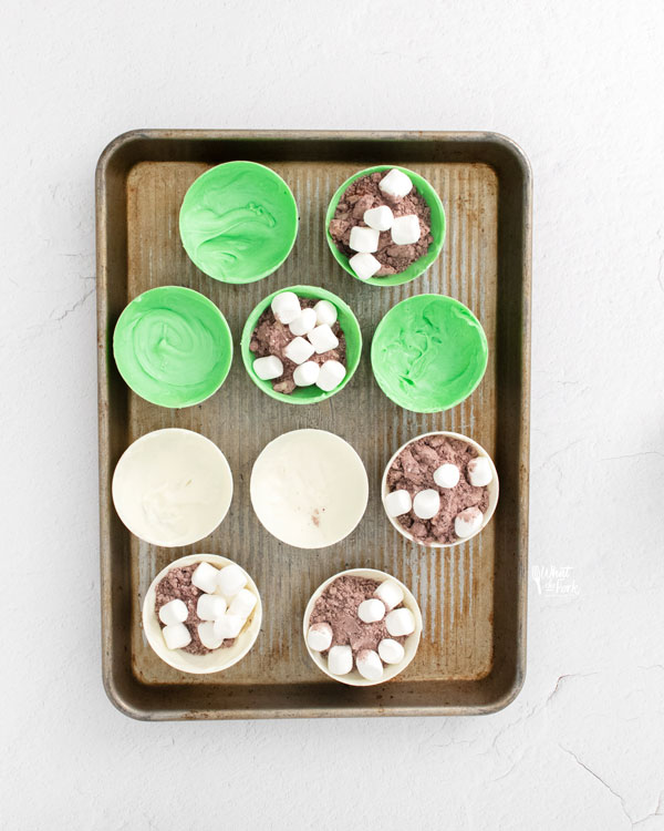 St. Patrick's Day Hot Cocoa Bombs on a metal sheet pan being assembled