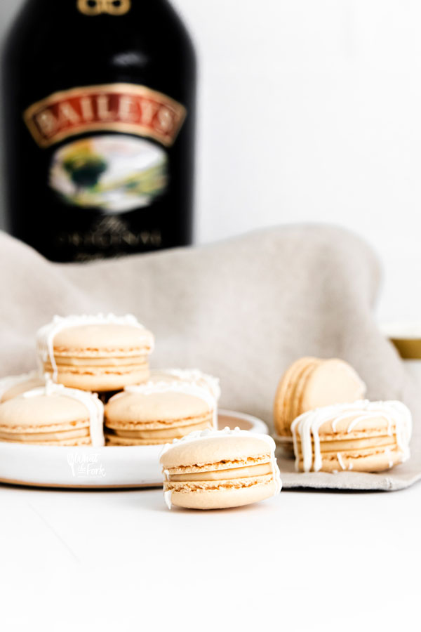 finished Baileys Irish Cream Macaron Recipe on a white plate and surface with a bottle of Baileys in the background
