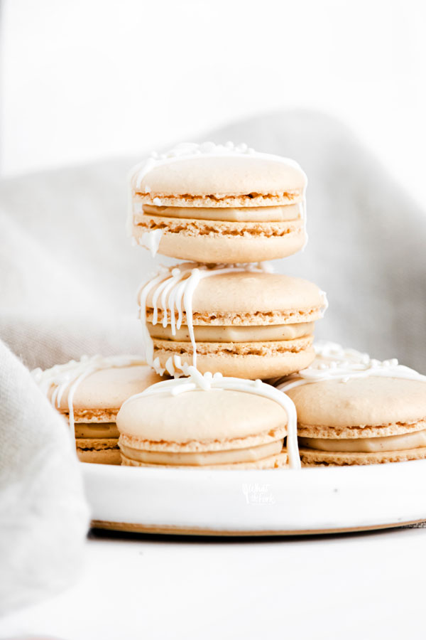 a baked Baileys Irish Cream Macaron Recipe with macarons stacked on a small white plate