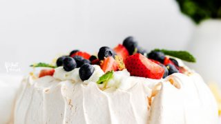 a finished classic pavlova recipe served on a white cake plate and topped with fresh berries and mint