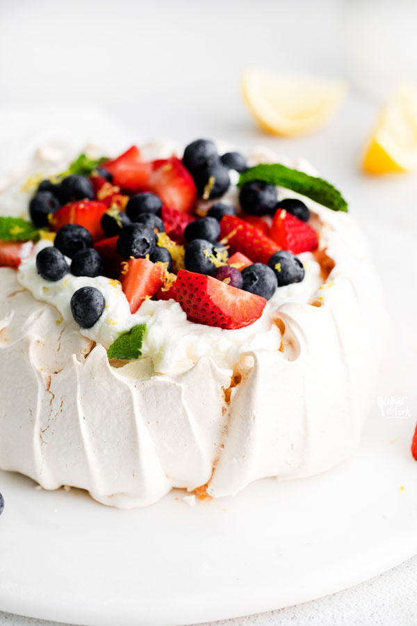 pavlova recipe being served on a flat white cake plate topped with fresh whipped cream, berries, fresh mint, and lemon zest