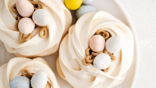 overhead shot of Easter Meringue Nests on a white plate with mini Cadbury Eggs